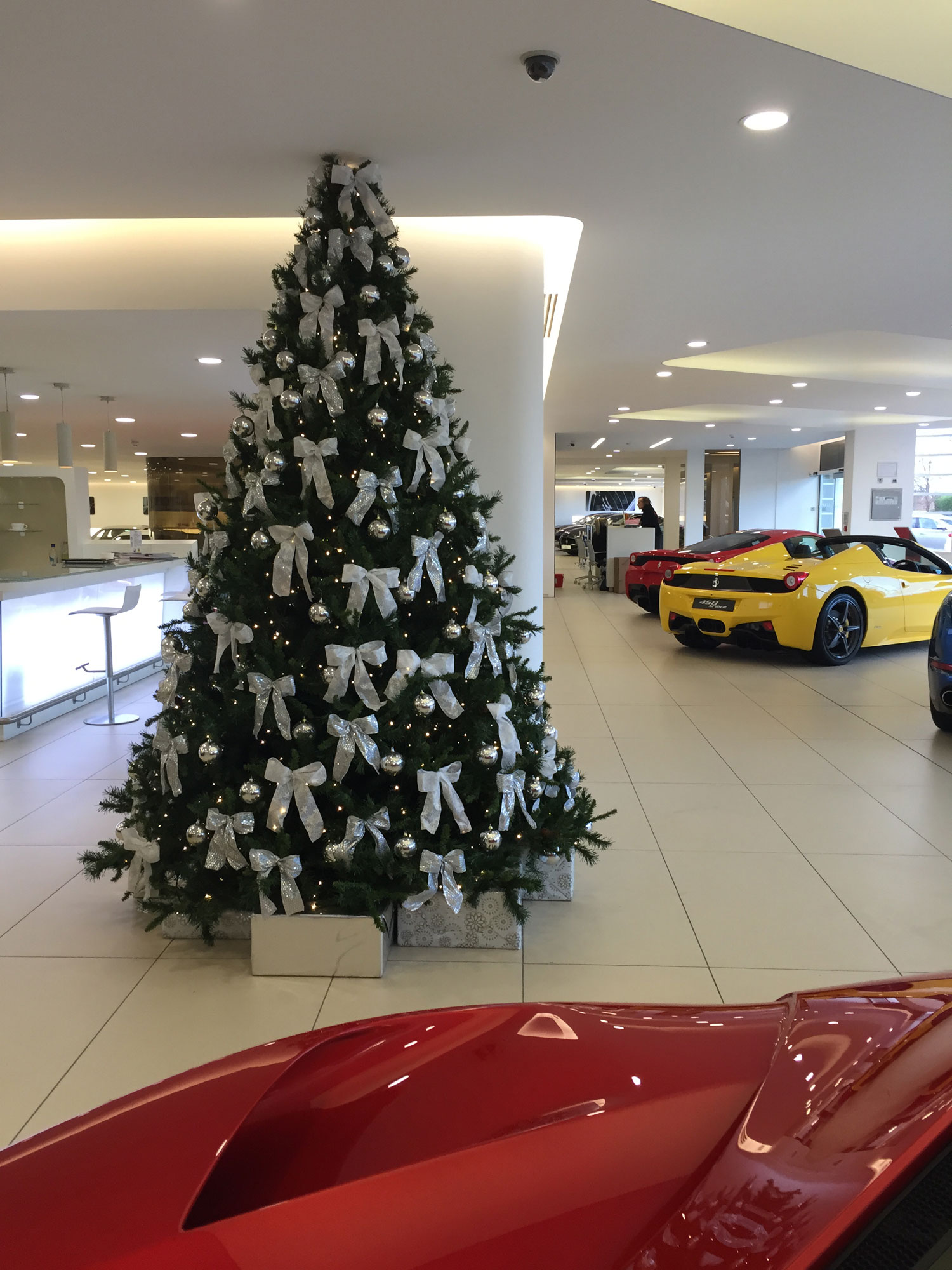christmas tree with white decorations in ferrari showroom